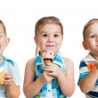 Happy children boy and girls eating ice cream in studio isolated — Stock Photo #19044491