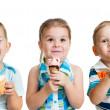 Happy children boy and girls eating ice cream in studio isolated — Stock Photo