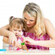 Happy little kid and mother sitting at table and playing with co — Stock Photo