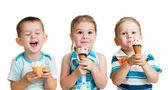 Happy children boy and girls eating ice cream in studio isolated — Stock Photo