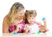 Happy little kid and mother sitting at table and playing with co — Stockfoto