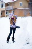 Child girl making snowman outdoors in front of house — Stok fotoğraf