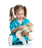 Adorable child with clothes of doctor examining hare toy over wh — Stock Photo