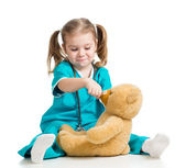 Adorable girl with clothes of doctor spoon feeding teddy bear ov — Stock Photo