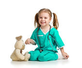 Adorable girl with clothes of doctor playing with toy over white — Стоковое фото