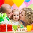 Parents kissing kid girl on birthday party - Stock Photo