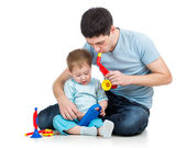 Father and baby boy having fun with musical toys. Isolated on wh — Stockfoto