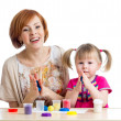 Happy child girl and mother sitting at table and playing with co — Stock Photo #19568833