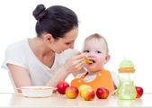 молодая мать, spoon-feeding ее девочка — Стоковое фото