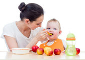 Młoda matka spoon-feeding jej córeczkę — Zdjęcie stockowe