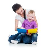 Glad mamma läser en bok till kid flicka — Stockfoto