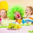 Kids celebrating birthday party with clown - Stock Photo
