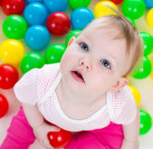 Portrait of cute baby girl playing among colorful balls — Stock Photo