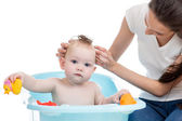 Mother washing her baby girl in the bathtub with foam — Stock Photo