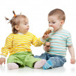 Foto Stock: Babies girl and boy eating ice cream together in studio isolated
