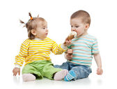 Babies girl and boy eating ice cream together in studio isolated — Stock Photo