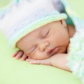 Adorable baby weared cap sleeping on green — Stock Photo
