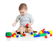 Cheerful child boy playing with construction set over white back — Stockfoto