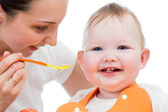 Young mother spoon-feeding happy daughter — Foto de Stock