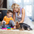 Foto de Stock  : Mother, child boy and pet dog playing together indoor