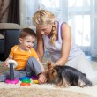 Mother, child boy and pet dog playing together indoor  — Stock Photo