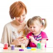 Stock Photo: Happy child girl and mother sitting at table and playing with co