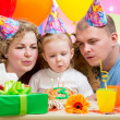 Kid girl with parents blow candles on birthday cake - Stock Photo