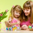 mother and daughter child painting easter eggs — Stock Photo
