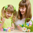 Mother and child girl paint easter eggs over green background — Stock Photo #21175455