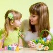 Mother and child girl paint easter eggs over green background — Stock Photo #21175459