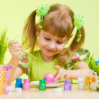 Cute smiling child girl painting Easter eggs on green background — Stock Photo