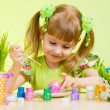Cute smiling child girl painting Easter eggs on green background - Stock Photo