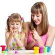 Foto Stock: Mother teeaching daughter to use colorful play dough