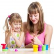 Happy kid girl and mother playing with colorful clay toy — Stock Photo