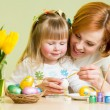 Happy mother teaches daughter to paint easter eggs  — Stock Photo