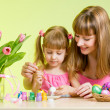 Mother and daughter kid painting easter eggs — Stock fotografie
