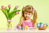 Cute kid girl painting Easter eggs — Stock Photo