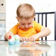 Child boy decorate easter eggs indoors — Stock Photo