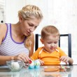 Mother with child boy decorate easter eggs — Stock Photo #21399981