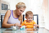 Mother with child boy decorate easter eggs — Stock Photo