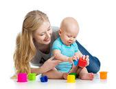 малыш мальчик и мать, играя вместе с кубка игрушки — Стоковое фото