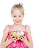 Cute smiling kid girl holding Easter eggs in basket — Stock Photo
