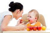 Mladá matka spoon-feeding jí holčička — Stock fotografie