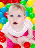 Portrait of funny baby playing among colorful balls — Stock Photo