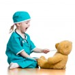 Adorable child dressed as doctor playing with toy over white — Stock Photo #21779567
