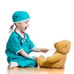 Прелестный ребенок, одетый как доктор, играя с игрушкой над белой — Стоковое фото