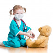 Child girl with clothes of doctor playing with toy — Stock Photo #21779633