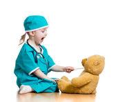 Adorável criança vestida como médico brincando com brinquedo sobre branco — Foto Stock