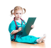 Child girl uniformed as doctor writing to clipboard isolated on — Stok fotoğraf