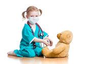 Child girl with clothes of doctor playing with toy — Stock Photo